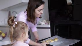 Glückliche Mutter unterrichtet Tochter, in der Küche zu kochen Mutter hält Behälter mit Plätzchen vor einem Ofen während Mädchenö stock video footage