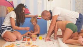 Glückliche Mutter, Vater und ihre kleinen Söhne, die mit Aquarellen im Kindertagesstättenraum malen Stockfotos