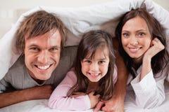 Glückliche Muttergesellschaft, die unter einem Duvet mit ihrer Tochter liegen stockbilder