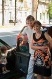 Glückliche Muttergesellschaft nähern sich einem neuen Auto und einem Kind hier Lizenzfreie Stockbilder