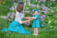 Glückliche Muttermutter mit der Tochter, die Zeit auf einem ehrfürchtigen Platz zwischen lila Spritzenbusch genießt Junge Damen m stockbild