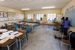 Glückliche namibische Schulkinder, die auf eine Lektion warten Stockfotografie