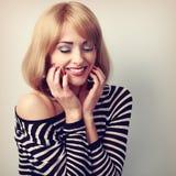 Glückliche natürliche lachende blonde Frau, die Make-upgesicht mit clos hält Stockfoto