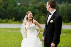 Glückliche nette elegante Paare auf dem erstaunlichen grünen Frühling des Hintergrundes Stockfotos