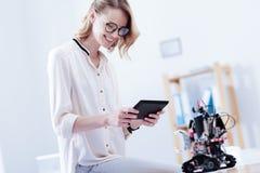 Glückliche nette Frau, die eine Tablette verwendet lizenzfreie stockfotografie