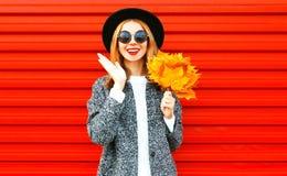 Glückliche nette Frau mit gelben Ahornblättern auf Rot Stockfotos