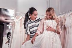 Glückliche nette Frauen, die ein Heiratskleid finden stockfoto