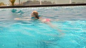 Glückliche nette junge Frau in der roten Schwimmenreihe im Swimmingpool Schönes sonniger Tagestürkiswasser stock video