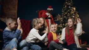 Glückliche nette Kinder, die fünf auf dem Hintergrund mit afrikanischem Mann im Weihnachtsmann-Kostüm spielen, lachen und geben stock video footage