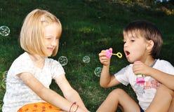 Glückliche nette Kinder, die mit Luftblasen spielen Stockfotos