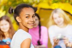 Glückliche nette Mädchennahaufnahme, die nahe gelbem Zelt sitzt Stockbild