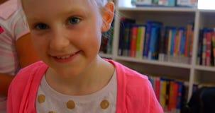 Glückliche nette Schulmädchenstellung in der Schulbibliothek 4k stock video