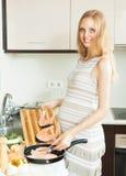 Glückliche nette schwangere Frau, die Lachse an der Küche kocht Stockbilder