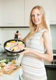 Glückliche nette schwangere Frau, die Lachse an der Küche kocht Lizenzfreies Stockbild