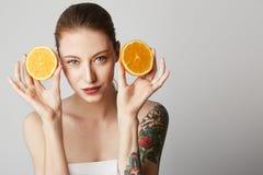 Glückliche nette tattoed junge Frau, die ihr rotes Haar betrachtet Kamera mit frohem und reizend Lächeln trägt Schönes Mädchen stockbilder