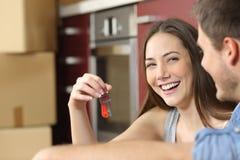 Glückliche neue flache Inhaber, die Schlüssel zeigen stockbilder