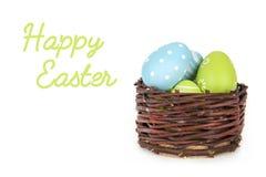 Glückliche Ostern-Aufschrift - wenige Eier auf dem hölzernen Korb auf dem weißen Hintergrund Lizenzfreie Stockbilder