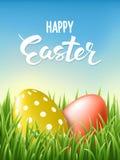 Glückliche Ostern-Beschriftungskarte verzierte Gold und rote Eier am frischen grünen Gras auf Hintergrund des blauen Himmels Stockfoto