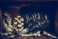 Glückliche Ostern-Grußkarte mit Wachteleiern im Glas und in der Tafel über rustikalem hölzernem Hintergrund lizenzfreie stockfotos