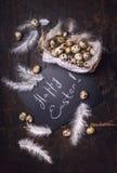 Glückliche Ostern-Grußkarte wird es auf Tafel und verzierte Wachteleier in Korb und in Federn geschrieben lizenzfreie stockfotografie