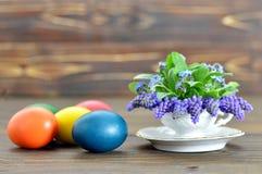 Glückliche Ostern-Karte mit farbigen Ostereiern und Feder blüht in der Teeschale Stockfotos