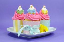 Glückliche Ostern-Rosa-, Gelbe und Blauekleine kuchen mit netten Hühnerdekorationen Stockfotos