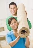 Glückliche Paar-tragende Teppich-Rolle Lizenzfreie Stockfotografie