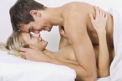 Glückliche Paare auf Bett Lizenzfreies Stockfoto