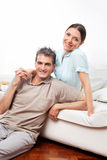 Glückliche Paare auf Couch beim Leben lizenzfreie stockfotografie