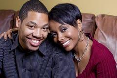 Glückliche Paare auf der Couch Stockfotografie