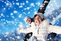 Glückliche Paare auf einem Winterhintergrund Lizenzfreie Stockfotos