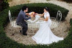 Glückliche Paare am Banketttisch auf Feld Stockfoto