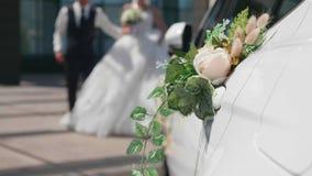 Glückliche Paare in der Weinlesekleidung Die Jungvermählten, die in Richtung zu ihrem Hochzeitsauto gehen stock video