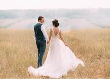 Glückliche Paare in der Weinlesekleidung Stilvolle junge Paare, die auf einen Hintergrund von wild lebenden Tieren bei Sonnenunte Lizenzfreie Stockfotografie