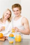 Glückliche Paare des Frühstücks bilden Orangensaftmorgen Stockfotos