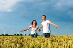 Glückliche Paare, die über grainfield laufen Lizenzfreie Stockbilder