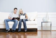Glückliche Paare, die auf Couch sich entspannen Stockfotos