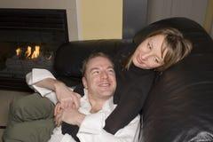 Glückliche Paare, die auf Couch sich entspannen Lizenzfreie Stockfotografie