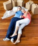 Glückliche Paare, die auf dem Fußboden in ihrem neuen Haus liegen Stockbild