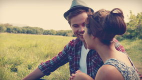 Glückliche Paare, die auf dem Gras sitzen stock footage