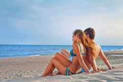 Glückliche Paare, die auf dem Strand sitzen Stockbild