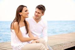 Glückliche Paare, die auf einem Pier sitzen Lizenzfreie Stockfotos