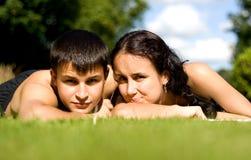 Glückliche Paare, die auf Gras liegen. Lizenzfreie Stockfotos