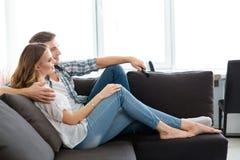 Glückliche Paare, die auf Sofa und überwachendem Fernsehapparat sitzen Stockfotografie