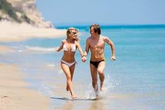 Glückliche Paare, die auf Strand laufen Stockfotos