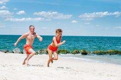 Glückliche Paare, die auf Strand laufen Mann und Frau, die auf dem Seeufer rütteln Lizenzfreie Stockbilder