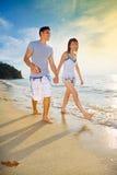Glückliche Paare, die das Gehen entlang Sonnenuntergangstrand genießen Stockfotos