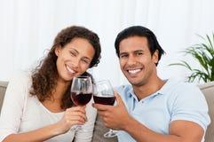 Glückliche Paare, die den Rotwein sitzt auf dem Sofa trinken lizenzfreie stockbilder
