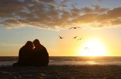 Glückliche Paare, die den Sonnenuntergang in der Liebe auf sein überwachen Lizenzfreie Stockfotos