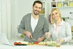 Glückliche Paare, die in der Küche kochen lizenzfreie stockbilder